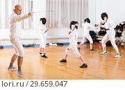 Купить «Coaches demonstrating to young athletes attack movements with rapier during fencing workout», фото № 29659047, снято 30 мая 2018 г. (c) Яков Филимонов / Фотобанк Лори