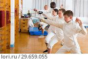Купить «Positive group of athletes at fencing workout», фото № 29659055, снято 30 мая 2018 г. (c) Яков Филимонов / Фотобанк Лори
