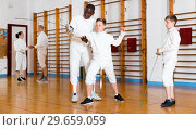 Купить «Focused boys fencers attentively listening to professional fencing coach in gym», фото № 29659059, снято 30 мая 2018 г. (c) Яков Филимонов / Фотобанк Лори