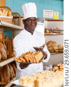 Купить «Baker in white uniform presenting baked products», фото № 29659071, снято 12 ноября 2018 г. (c) Яков Филимонов / Фотобанк Лори