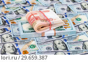 Купить «Folded five thousandths banknotes of russian roubles over heap of one hundred american dollar bills», фото № 29659387, снято 4 января 2017 г. (c) FotograFF / Фотобанк Лори