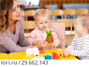Kindergarten teacher playing with nursery kids at table. Стоковое фото, фотограф Оксана Кузьмина / Фотобанк Лори