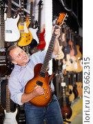 Купить «Man choosing electric guitar», фото № 29662315, снято 18 сентября 2017 г. (c) Яков Филимонов / Фотобанк Лори