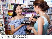 Купить «Stylish woman and girl choosing eyeshadows in cosmetics shop», фото № 29662351, снято 21 июня 2018 г. (c) Яков Филимонов / Фотобанк Лори