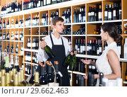 Купить «portrait of male seller showing bottle of wine to female customer in wine shop», фото № 29662463, снято 20 мая 2019 г. (c) Яков Филимонов / Фотобанк Лори
