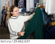 Купить «Woman choosing new overcoat in store», фото № 29662631, снято 6 декабря 2018 г. (c) Яков Филимонов / Фотобанк Лори