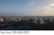 Купить «Aerial scene of built-up city with coast and sea in foreground. Antalya, Turkey», видеоролик № 29663091, снято 1 августа 2018 г. (c) Данил Руденко / Фотобанк Лори
