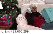 Купить «Woman with Christmas Presents», видеоролик № 29666299, снято 26 февраля 2008 г. (c) Wavebreak Media / Фотобанк Лори