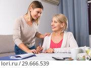 Купить «Daughter helps mother to lead home accounting», фото № 29666539, снято 13 ноября 2017 г. (c) Яков Филимонов / Фотобанк Лори