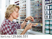 Mature glad woman customer picking various buttons. Стоковое фото, фотограф Яков Филимонов / Фотобанк Лори
