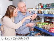 Купить «woman and man picking variety candies», фото № 29666699, снято 11 апреля 2018 г. (c) Яков Филимонов / Фотобанк Лори