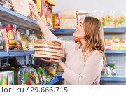 Купить «Adult positive woman buyer with cake layers of grocery food store», фото № 29666715, снято 11 апреля 2018 г. (c) Яков Филимонов / Фотобанк Лори