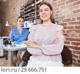 Купить «Smiling girl client in nail salon, manicure master on background», фото № 29666751, снято 30 мая 2018 г. (c) Яков Филимонов / Фотобанк Лори