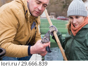 Купить «Owner of sturgeon farm with worker inspecting fish», фото № 29666839, снято 4 февраля 2018 г. (c) Яков Филимонов / Фотобанк Лори