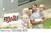 Купить «Young family in front of their house», видеоролик № 29668455, снято 5 апреля 2009 г. (c) Wavebreak Media / Фотобанк Лори