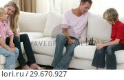 Купить «Father and son playing chess on the sofa with mother and sister», видеоролик № 29670927, снято 13 октября 2009 г. (c) Wavebreak Media / Фотобанк Лори