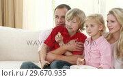Купить «Family watching television and eating crisps at home», видеоролик № 29670935, снято 13 октября 2009 г. (c) Wavebreak Media / Фотобанк Лори