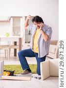 Купить «Young handsome man repairing chair at home», фото № 29671299, снято 30 октября 2018 г. (c) Elnur / Фотобанк Лори
