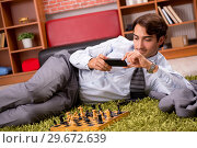 Купить «Young handsome boss playing chess during break», фото № 29672639, снято 10 сентября 2018 г. (c) Elnur / Фотобанк Лори