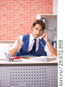 Купить «Young handsome employee working in the office», фото № 29672859, снято 12 сентября 2018 г. (c) Elnur / Фотобанк Лори
