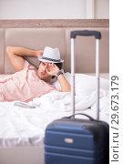Купить «Man with suitcase in bedroom waiting for trip», фото № 29673179, снято 17 сентября 2018 г. (c) Elnur / Фотобанк Лори
