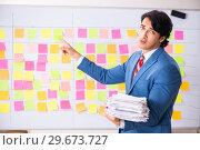 Купить «Young handsome employee with many conflicting priorities», фото № 29673727, снято 16 октября 2018 г. (c) Elnur / Фотобанк Лори