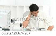 Купить «Young businessman stressed with so many bills to pay», видеоролик № 29674267, снято 22 апреля 2019 г. (c) Wavebreak Media / Фотобанк Лори