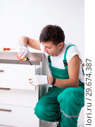 Купить «Young worker with cupboard in home renovation concept», фото № 29674387, снято 17 октября 2018 г. (c) Elnur / Фотобанк Лори
