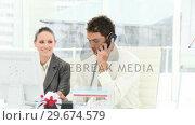 Купить «Two smiling colleagues on phone working at a computer», видеоролик № 29674579, снято 17 января 2020 г. (c) Wavebreak Media / Фотобанк Лори