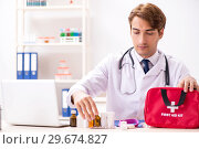 Купить «Young doctor with first aid kit in hospital», фото № 29674827, снято 23 августа 2018 г. (c) Elnur / Фотобанк Лори