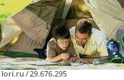 Купить «Dad and son looking at a map in front of a tent», видеоролик № 29676295, снято 10 ноября 2010 г. (c) Wavebreak Media / Фотобанк Лори