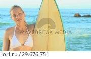 Купить «Beautiful blonde woman posing with her surfboard», видеоролик № 29676751, снято 15 ноября 2010 г. (c) Wavebreak Media / Фотобанк Лори