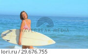 Купить «Pretty darkhaired woman posing with her surfboard», видеоролик № 29676755, снято 15 ноября 2010 г. (c) Wavebreak Media / Фотобанк Лори