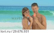 Купить «Sweet couple eating water ices with their backs to the sea», видеоролик № 29676931, снято 15 ноября 2010 г. (c) Wavebreak Media / Фотобанк Лори