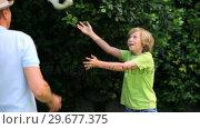 Купить «Man and son playing with a soccer ball in garden», видеоролик № 29677375, снято 6 ноября 2010 г. (c) Wavebreak Media / Фотобанк Лори