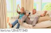 Купить «Couple on sofa ecstatic as they watch a programme on TV», видеоролик № 29677543, снято 6 ноября 2010 г. (c) Wavebreak Media / Фотобанк Лори
