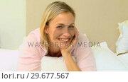 Купить «Blonde young woman posing while her husband is reading», видеоролик № 29677567, снято 6 ноября 2010 г. (c) Wavebreak Media / Фотобанк Лори