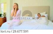 Купить «Young woman on bed seeking serenity while hubsand sleeps», видеоролик № 29677591, снято 6 ноября 2010 г. (c) Wavebreak Media / Фотобанк Лори