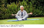 Купить «Mature woman doing yoga outdoors on a mat », видеоролик № 29677671, снято 6 ноября 2010 г. (c) Wavebreak Media / Фотобанк Лори