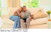 Купить «Young couple on sofa laughing over their laptop», видеоролик № 29677723, снято 6 ноября 2010 г. (c) Wavebreak Media / Фотобанк Лори