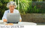 Retired woman using a laptop outdoors. Стоковое видео, агентство Wavebreak Media / Фотобанк Лори