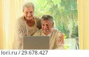 Купить «Mature couple smiling about something on a laptop», видеоролик № 29678427, снято 5 ноября 2010 г. (c) Wavebreak Media / Фотобанк Лори