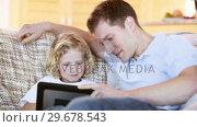 Купить «Smiling father using a tablet computer with his son», видеоролик № 29678543, снято 2 ноября 2011 г. (c) Wavebreak Media / Фотобанк Лори