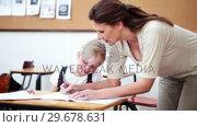 Купить «Teacher helping a pupil», видеоролик № 29678631, снято 5 ноября 2011 г. (c) Wavebreak Media / Фотобанк Лори
