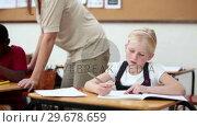 Купить «Teacher helping her pupil», видеоролик № 29678659, снято 5 ноября 2011 г. (c) Wavebreak Media / Фотобанк Лори