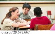 Купить «Smiling teacher talking with a pupil», видеоролик № 29678667, снято 5 ноября 2011 г. (c) Wavebreak Media / Фотобанк Лори