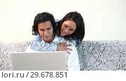 Купить «Woman hugging her boyfriend that is using the laptop on the sofa», видеоролик № 29678851, снято 3 ноября 2011 г. (c) Wavebreak Media / Фотобанк Лори