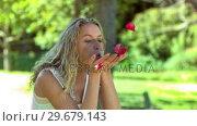 Blonde woman in slow motion blowing on petals. Стоковое видео, агентство Wavebreak Media / Фотобанк Лори