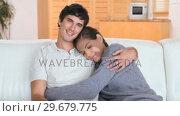 Купить «Couple sitting together on a couch», видеоролик № 29679775, снято 4 ноября 2011 г. (c) Wavebreak Media / Фотобанк Лори