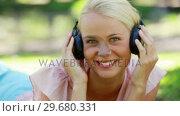 Купить «Close up of a woman listening to music and moving her head to the rhythm », видеоролик № 29680331, снято 17 ноября 2011 г. (c) Wavebreak Media / Фотобанк Лори